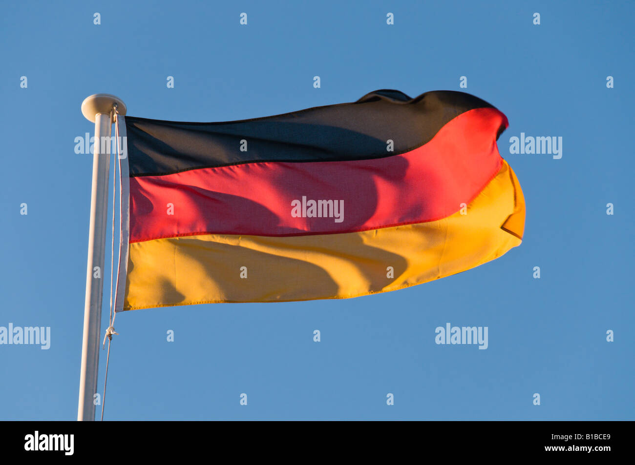 A German Flag Blowing In the Wind On A Blue Sky Background - Stock Image