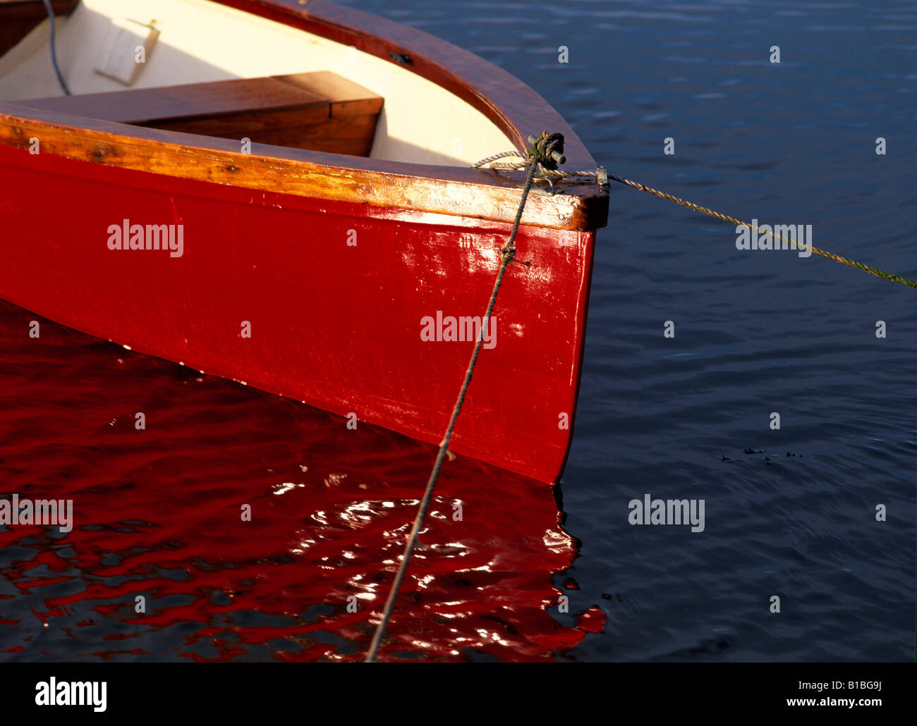 A bright red rowing boat catching the evening sun and reflected in the water - Stock Image