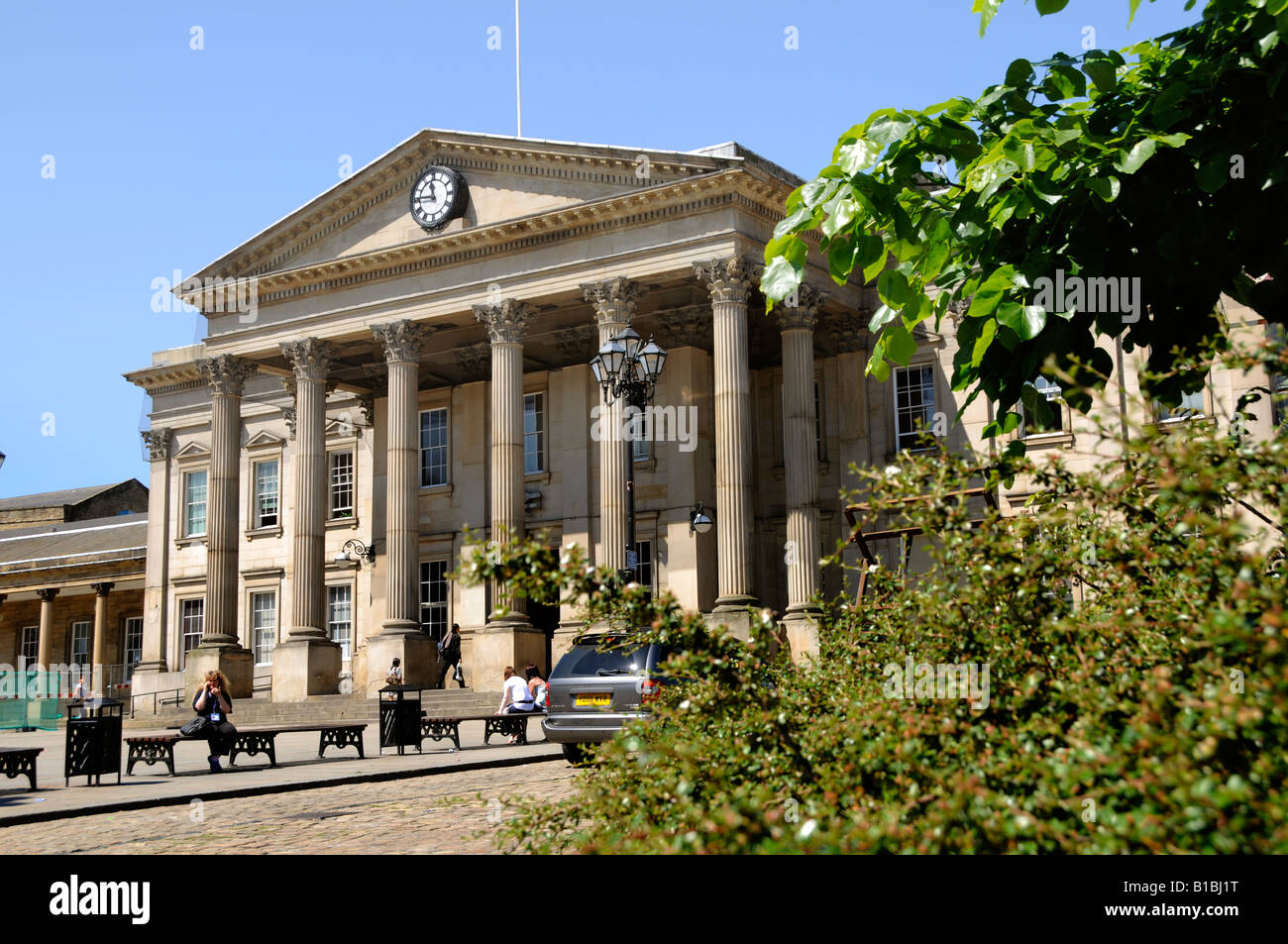 The classical colonnade and portico of the grand entrance of the  Victorian railway station seen beyond foliage - Stock Image