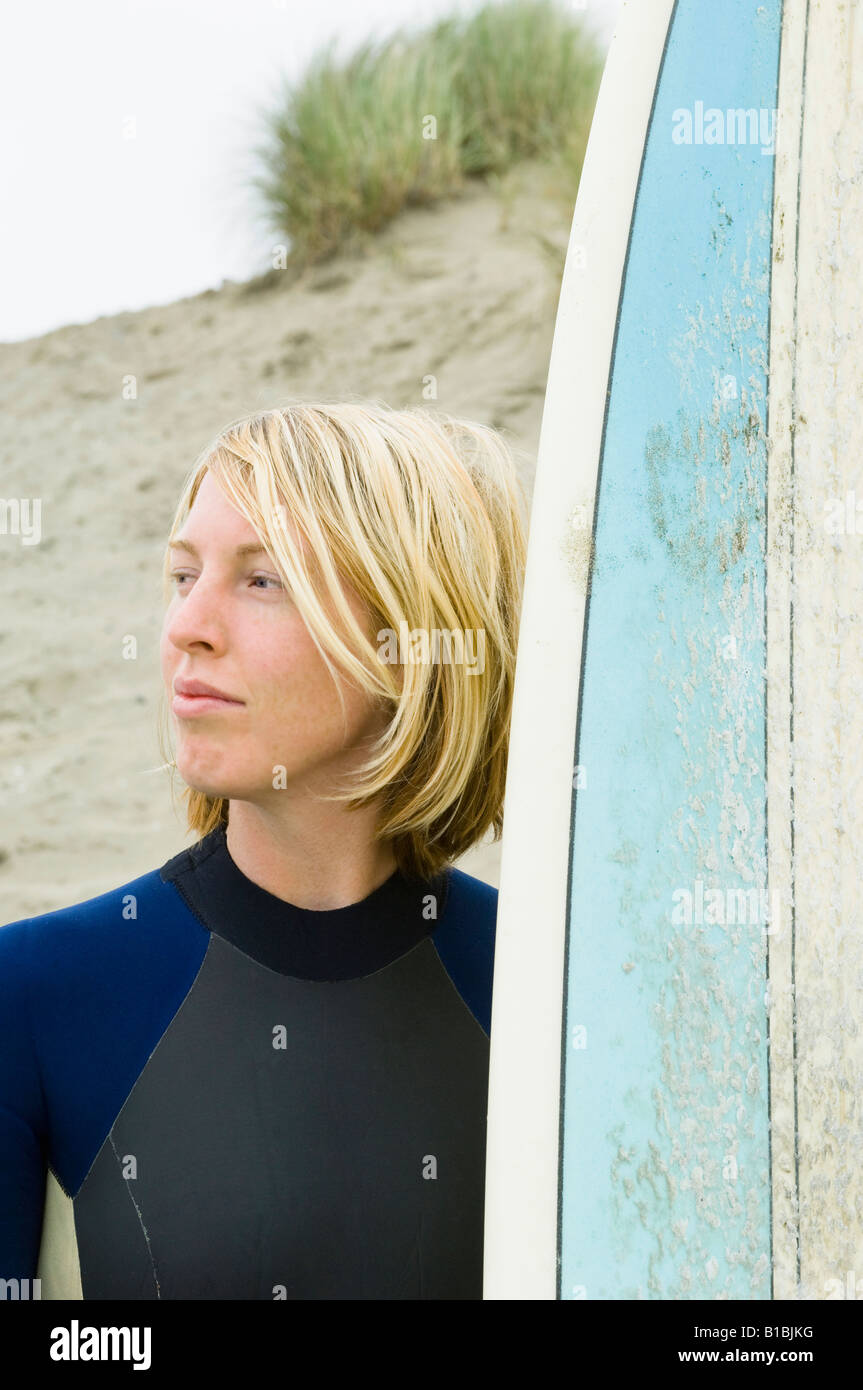 Blonde surfer woman in wetsuit with surfboard at the beach. - Stock Image