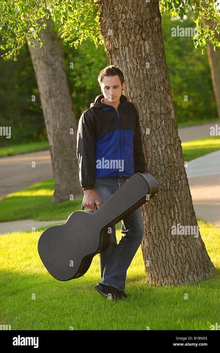 Man posed with his guitar case - Stock Image