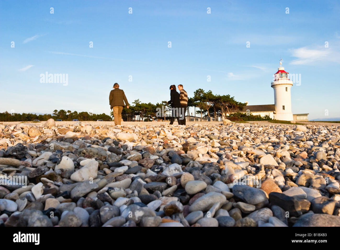 Lighthouse and a family walking on the beach - Stock Image
