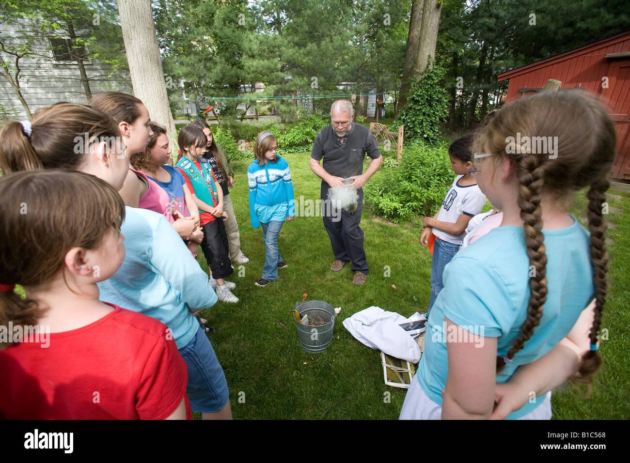 Beekeeper Rich Wieske teaches members of a Girl Scout troop about honey bees and beekeeping - Stock Image