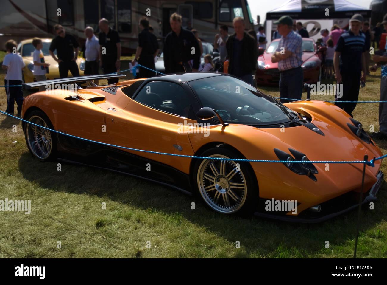 An interested crowd gather around an orange Pagani Zonda F Roadster