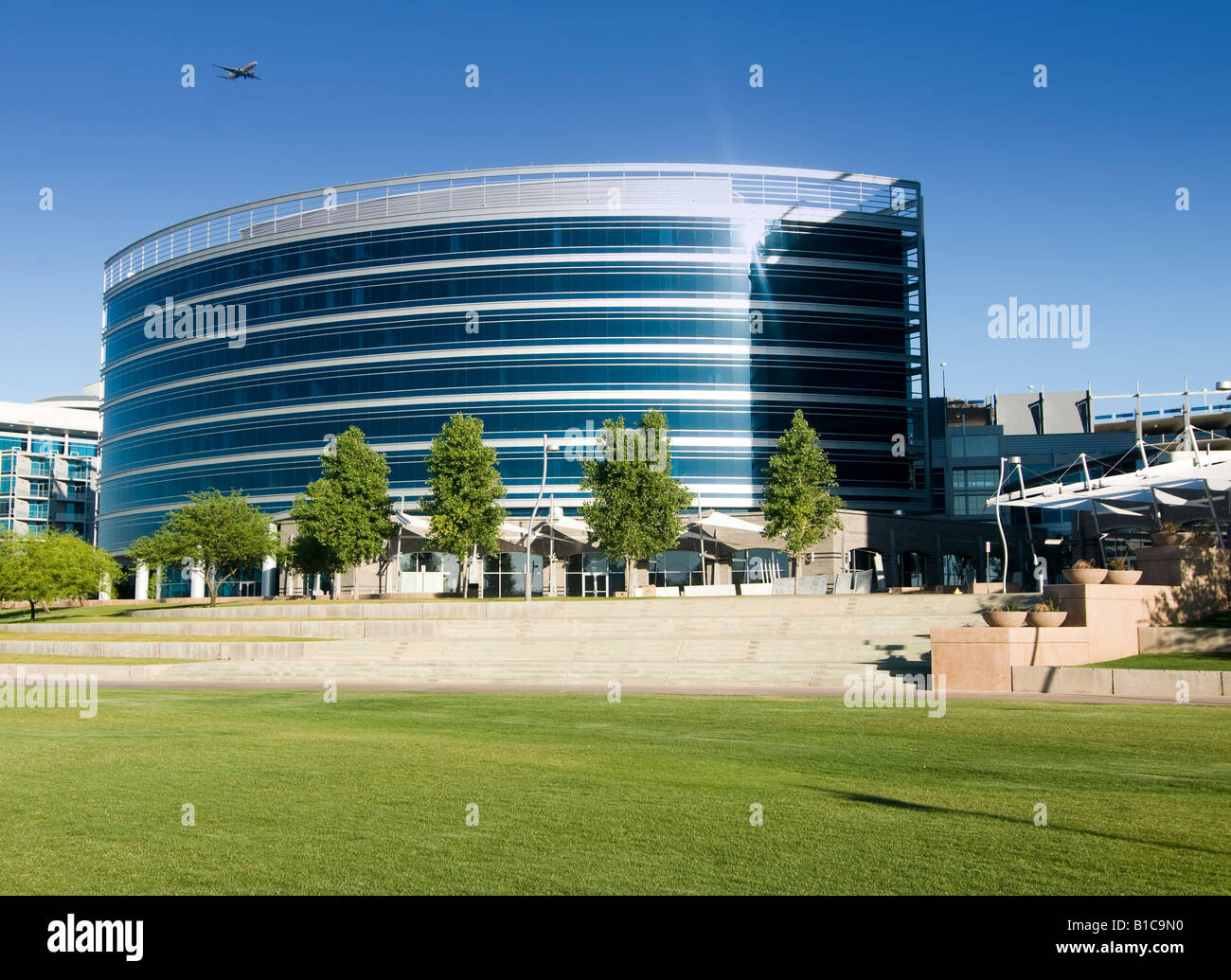 Skyscraper development in downtown Tempe, AZ located by town lake, with aircraft in sky. - Stock Image