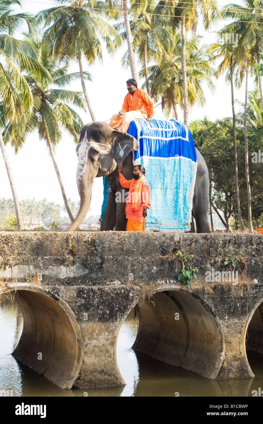 2 indian sadhus in goa on elephant holy men religion religous orange robes ochre - Stock Image