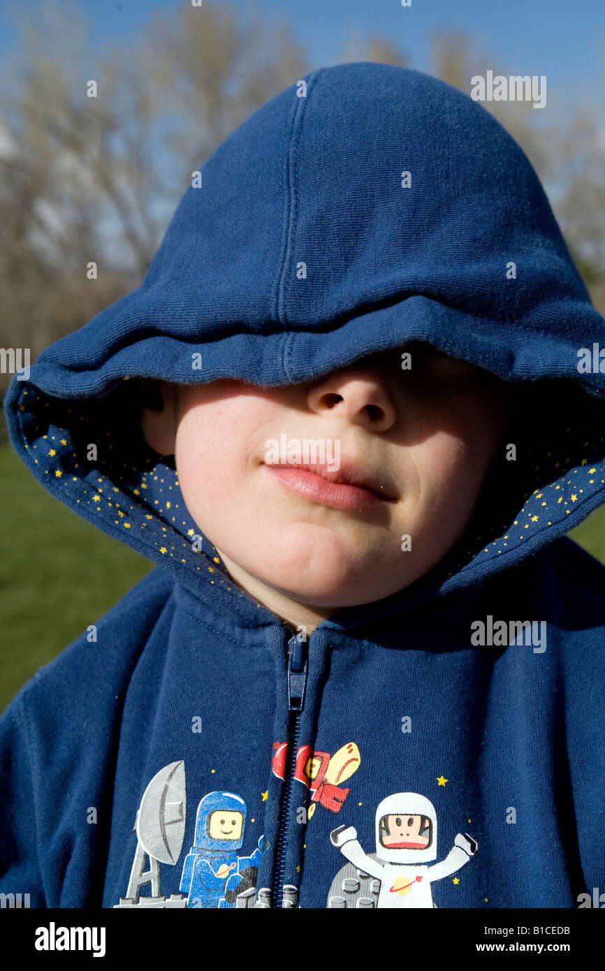 A young boy in a hood covers his face with his hands Stock Photo ... 715e01416fe2