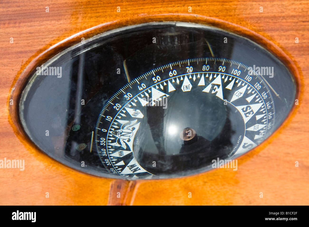 An old compass behind glass and the polished wood of its binnacle on the schooner Pride of Baltimore II. - Stock Image