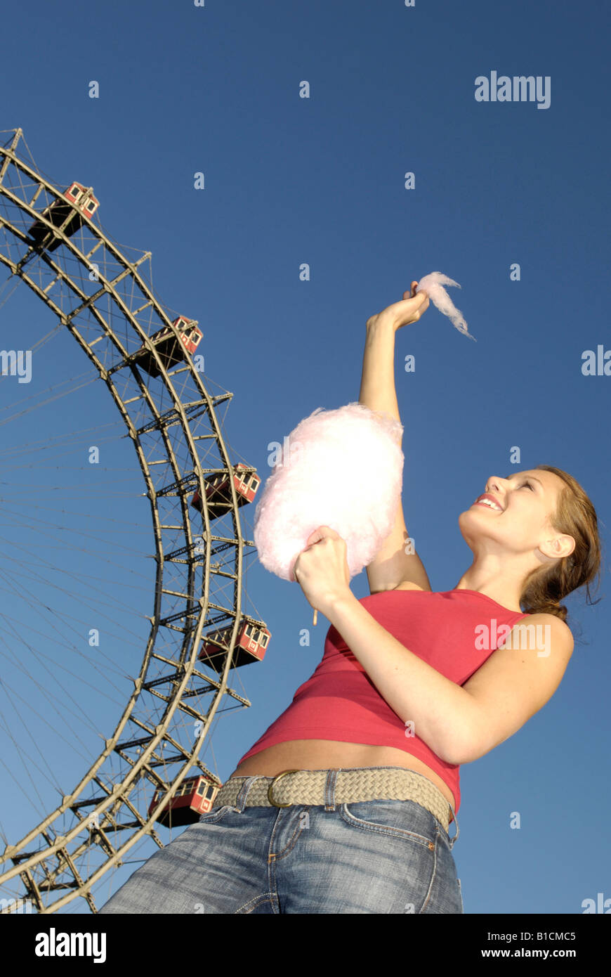 happy young woman with candy floss in front of the Wiener Riesenrad auf dem Prater, Austria, Vienna Stock Photo