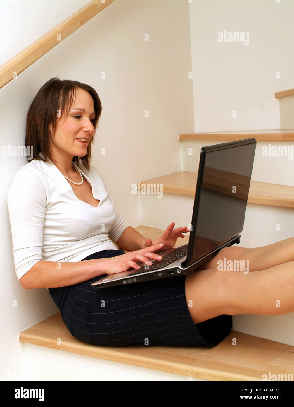 Young business woman sitting on stairs and using laptop - Stock Image