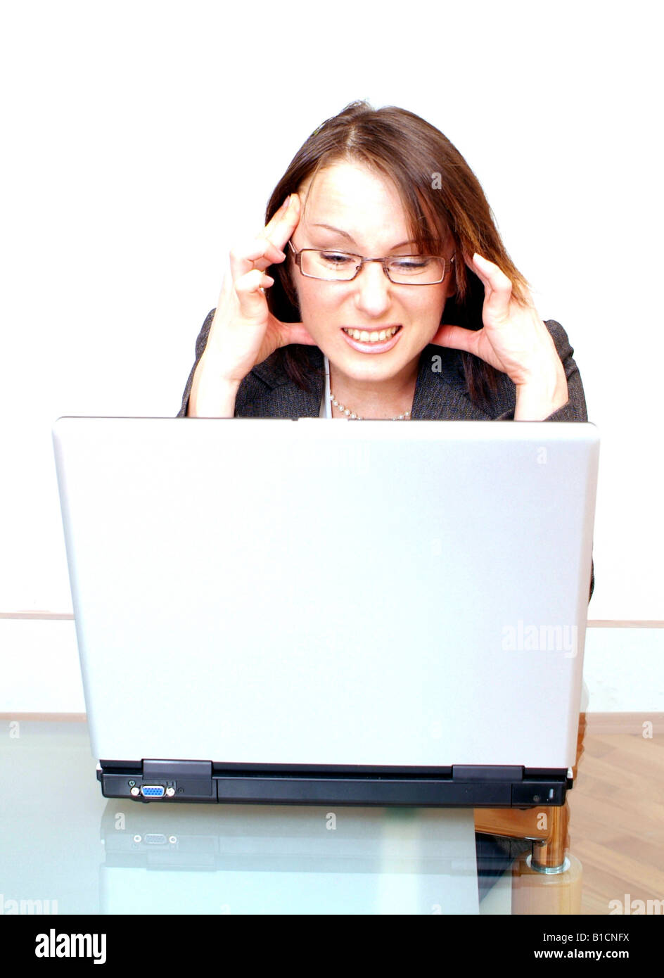 strained businesswoman using laptop - Stock Image