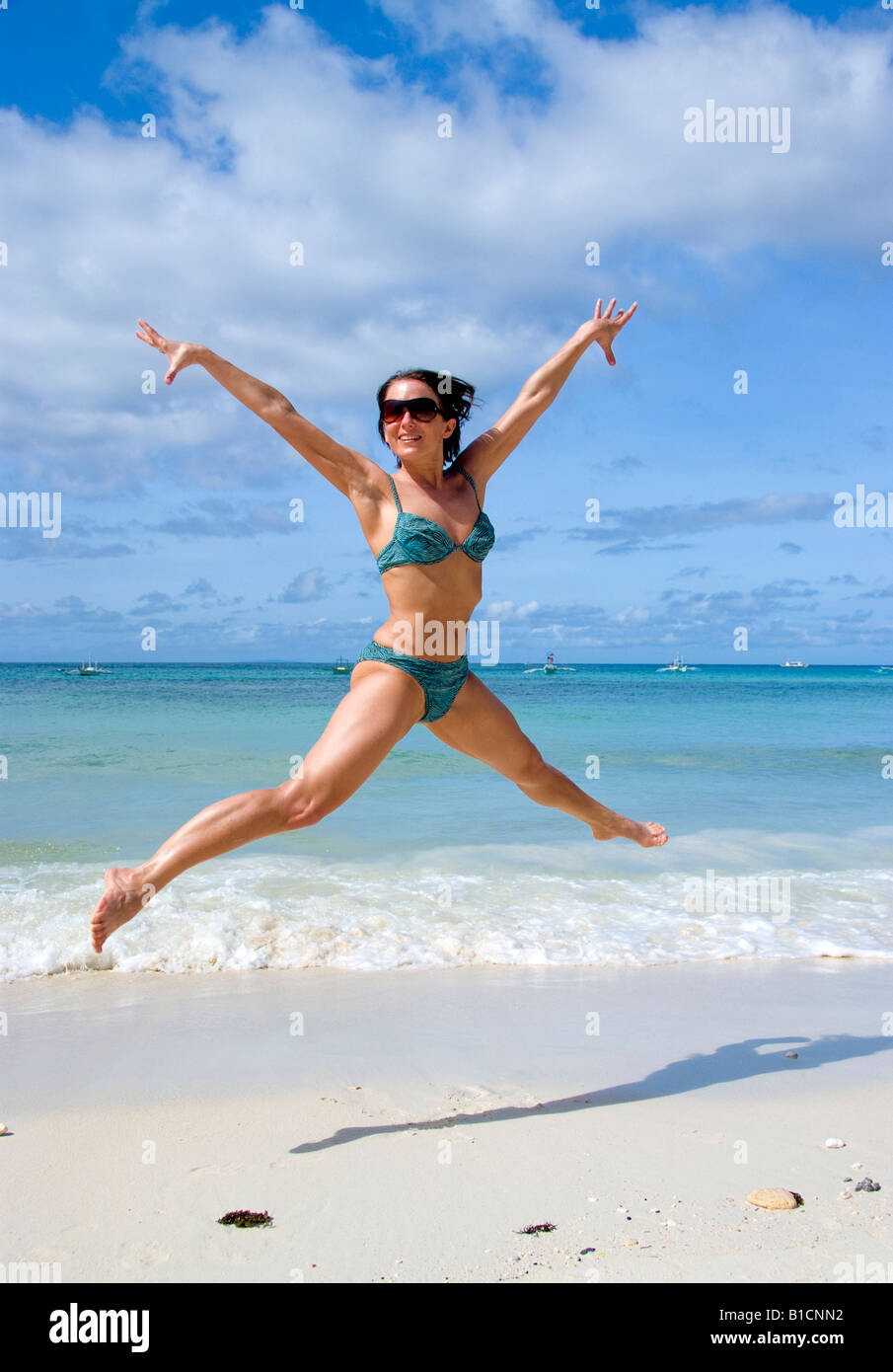 young woman jumping on the beach, Philippines - Stock Image