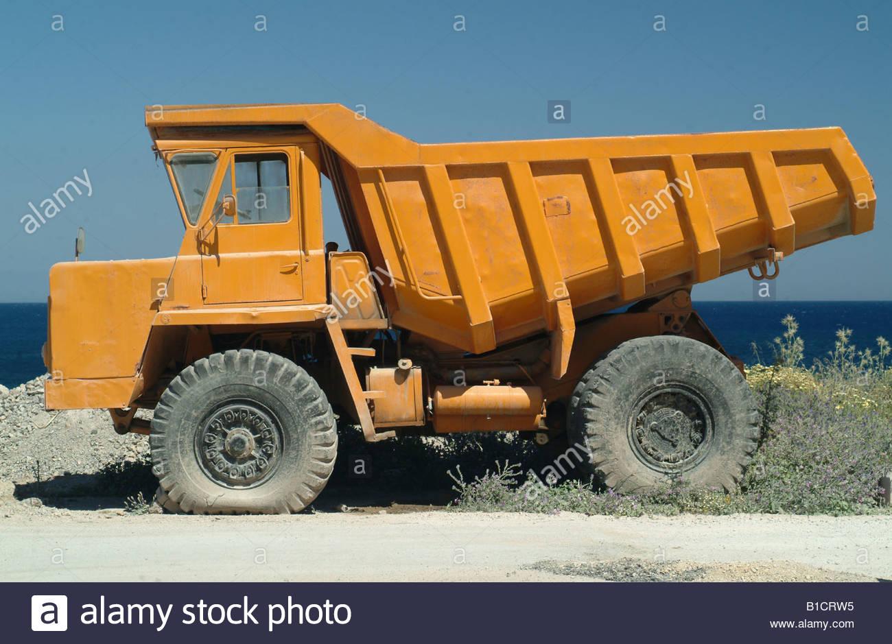 Large heavy duty yellow tipper lorry vehicle truck trucks Orange lorry dump truck dumper Construction nice photo - Stock Image