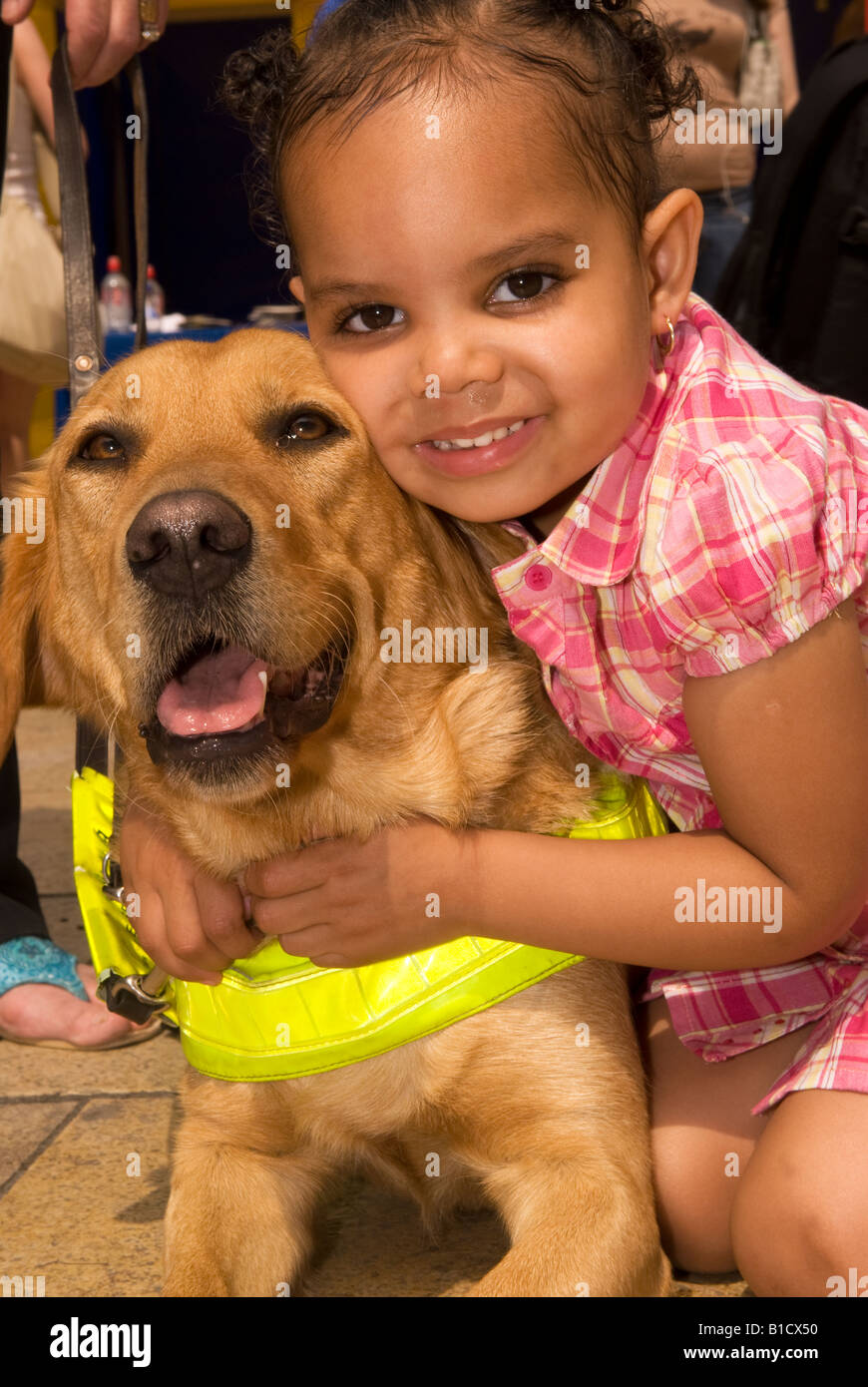 Young black girl cuddling guide dog, Hammersmith, west London, UK. - Stock Image