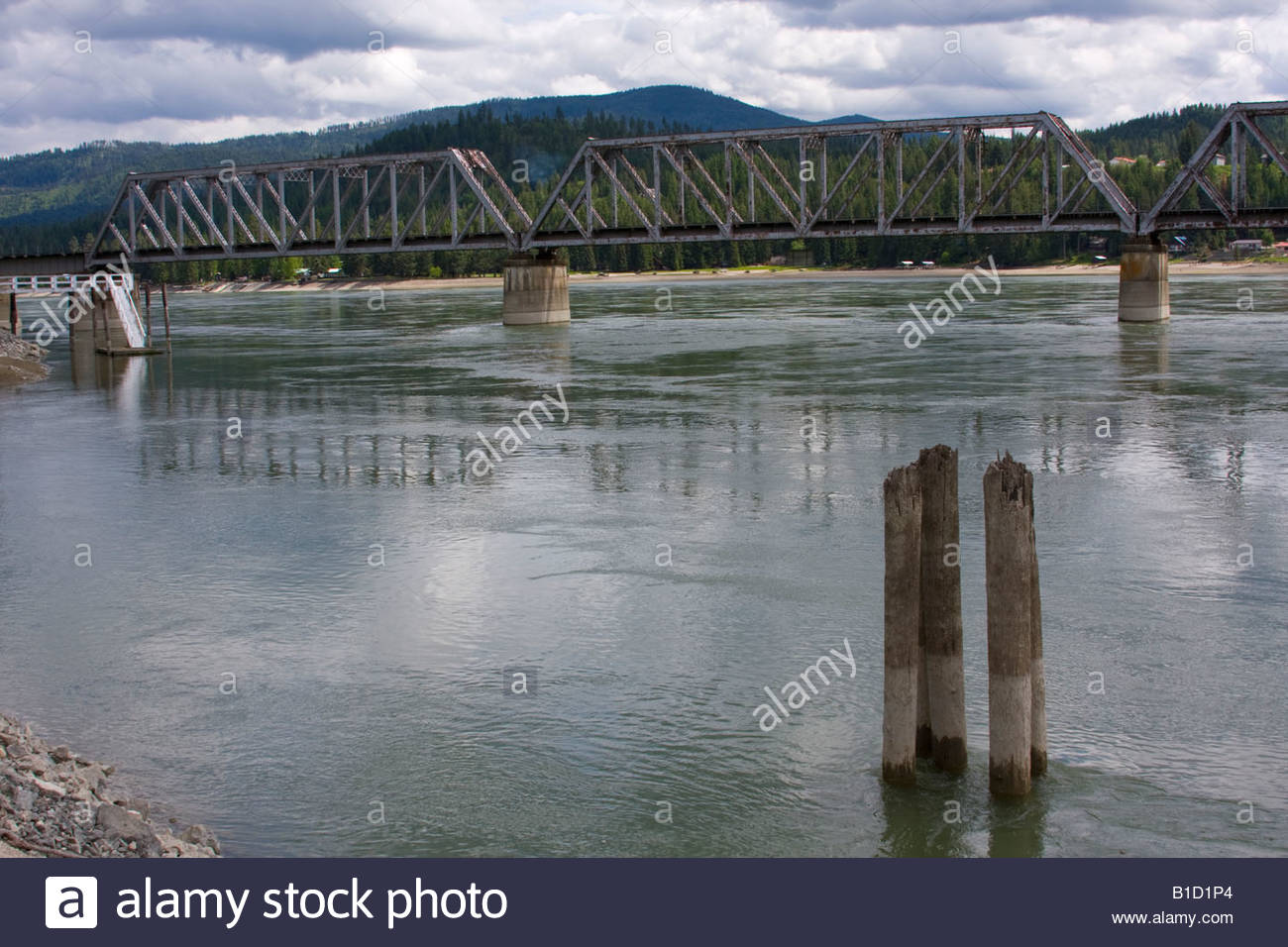 Railroad bridge over the Pend Oreille River in North Idaho on a cloudy day with pilings in the foreground. - Stock Image