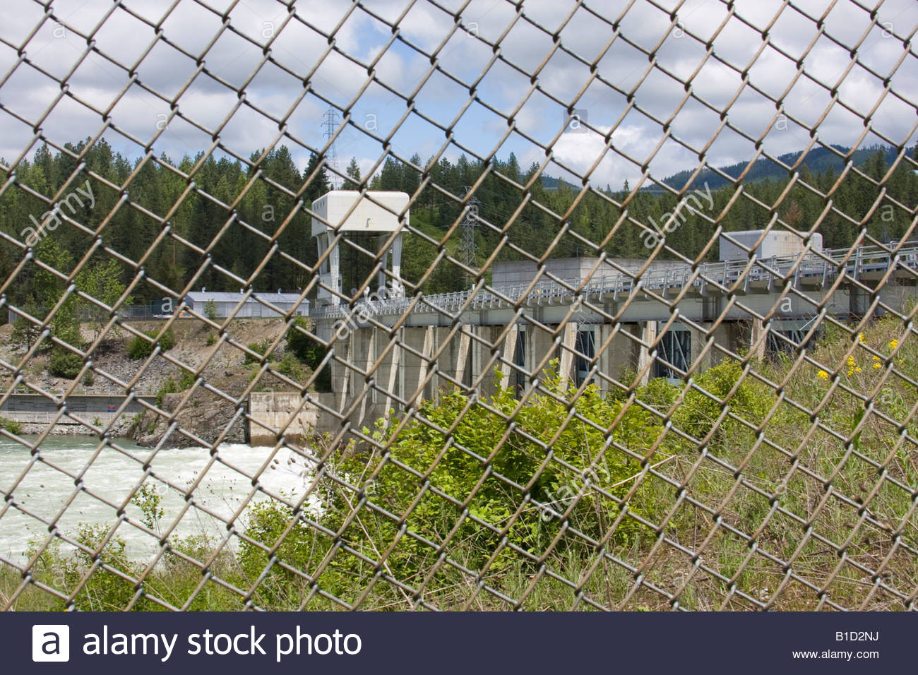 The Albeni Falls Dam seen from the south side of the Pend Oreille River through a chain link fence. North Idaho, - Stock Image