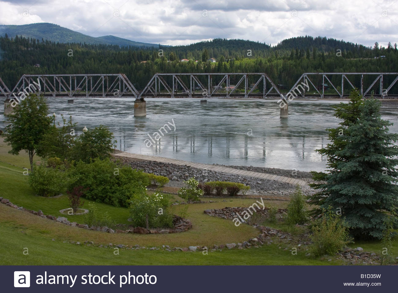 Railroad bridge over the Pend Oreille River in North Idaho with a grassy path in the foreground. - Stock Image