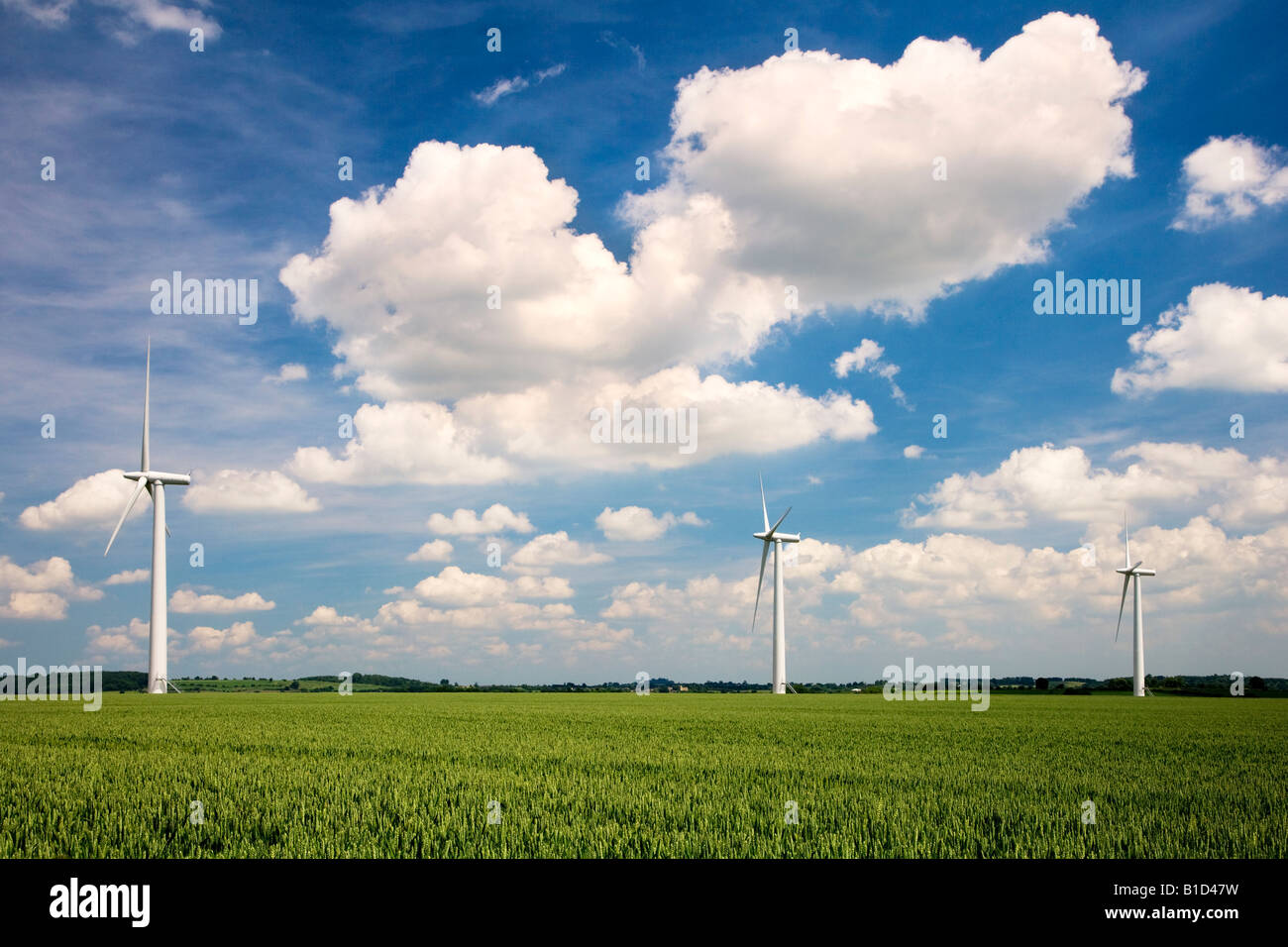 Three wind turbines in a field of wheat against a summer sky on an inshore wind farm in Oxfordshire, England, UK Stock Photo