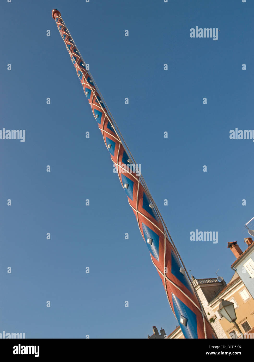 colourful flagpole flagstaff on the market place in the old town of Cres in Croatia - Stock Image