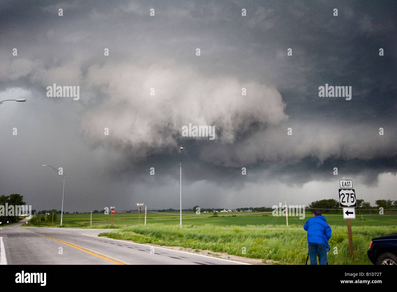 A wall cloud forms on a squall line near Valley Nebraska June 11 2008 as a storm chaser films in the forground - Stock Image