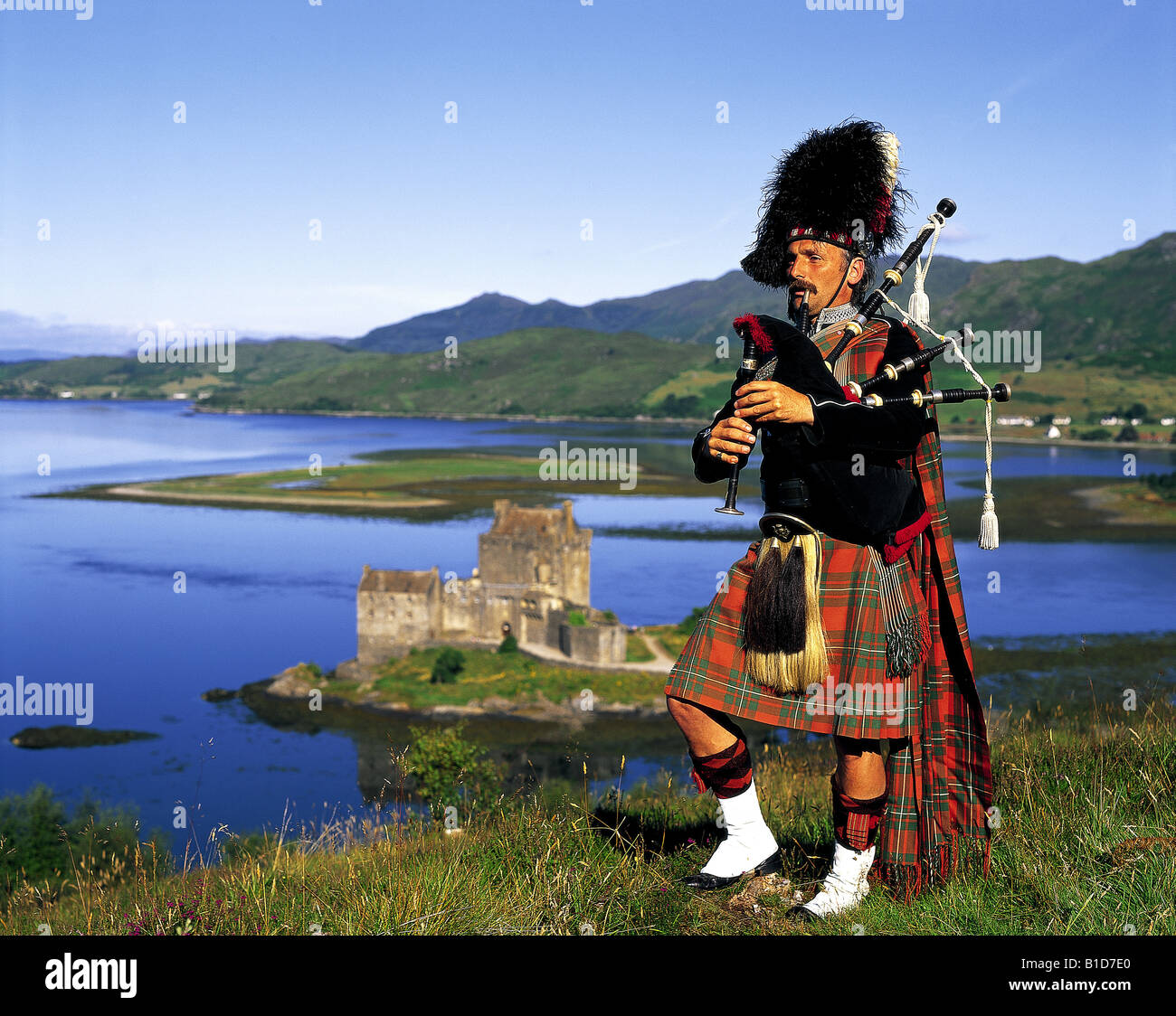 Scottish bagpiper on hill above Eilean Donan Castle Scotland Stock Photo