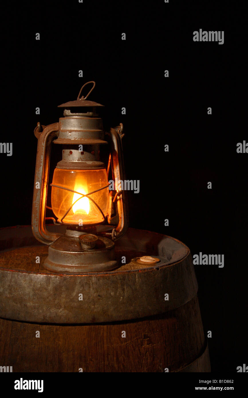 An oil lamp standing on a barrel in the darkness. - Stock Image