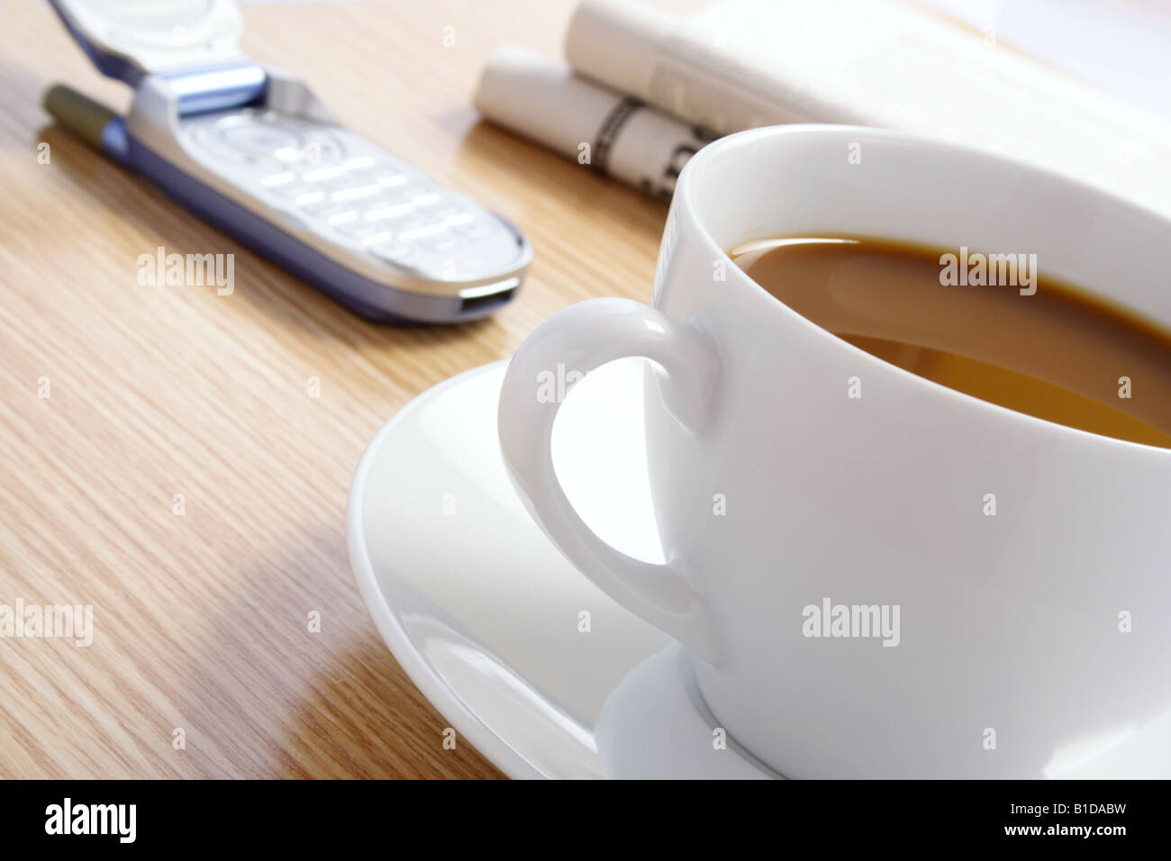 Coffee Cellphone and Newspaper on Desk Stock Photo