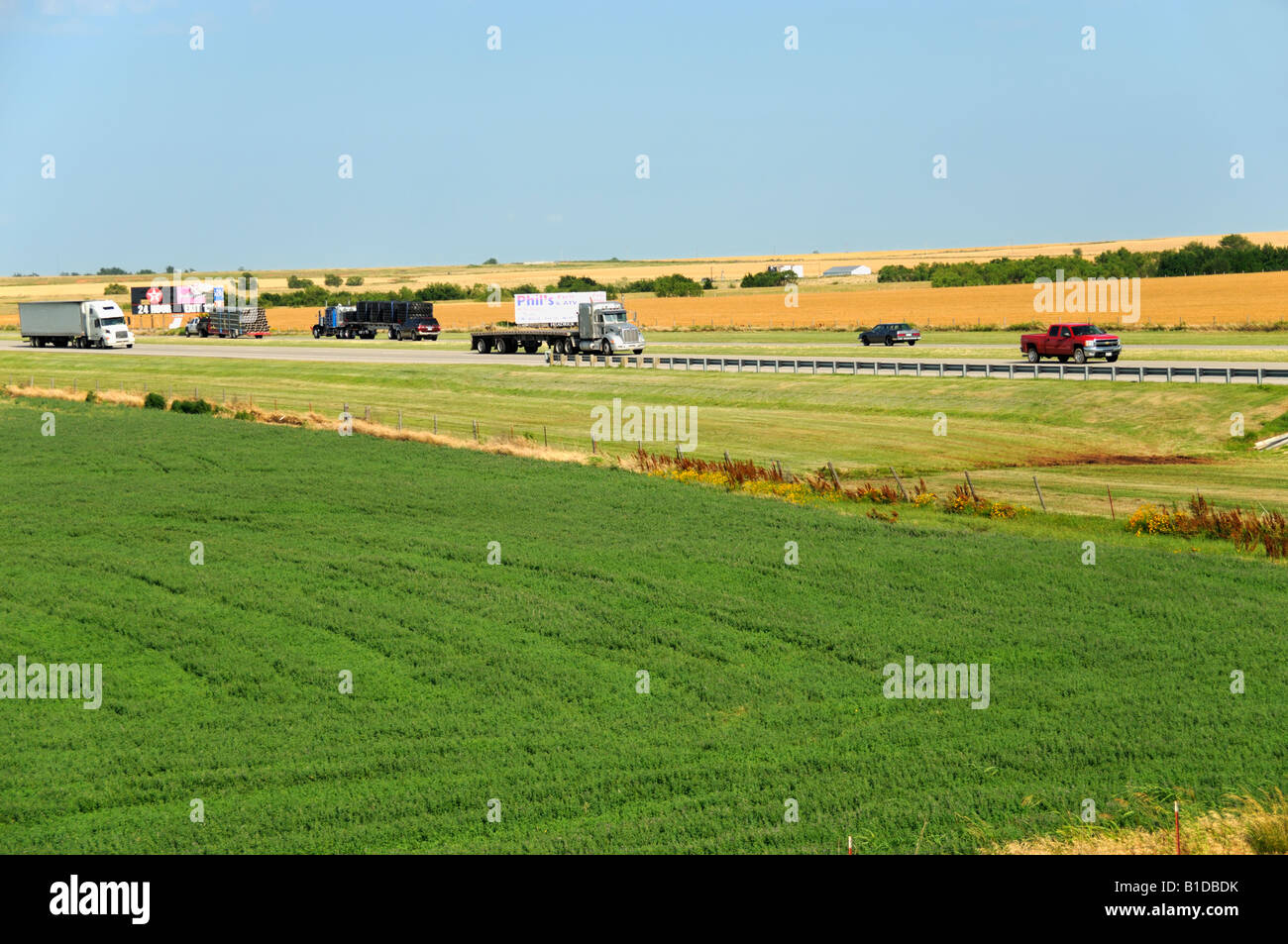Interstate 40 in central Oklahoma, heavily used by the trucking industry. Here it cuts between wheat and alfalfa - Stock Image