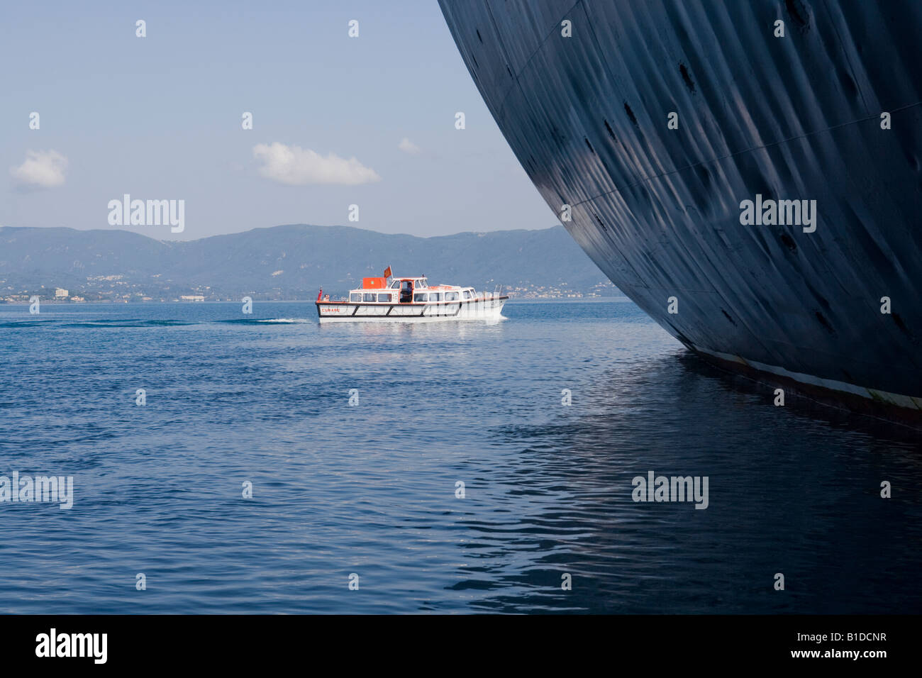 Close up of the Stern of the Cunard QE2 showing the buckling to the side of the ship and the waterline with ships - Stock Image