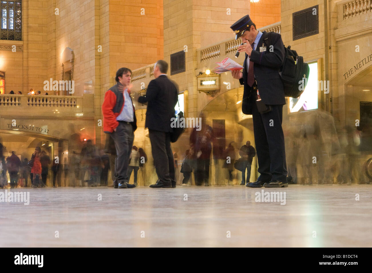 Low angle long exposure shot of passengers moving around in Grand Central Station, New York with railway guard in - Stock Image