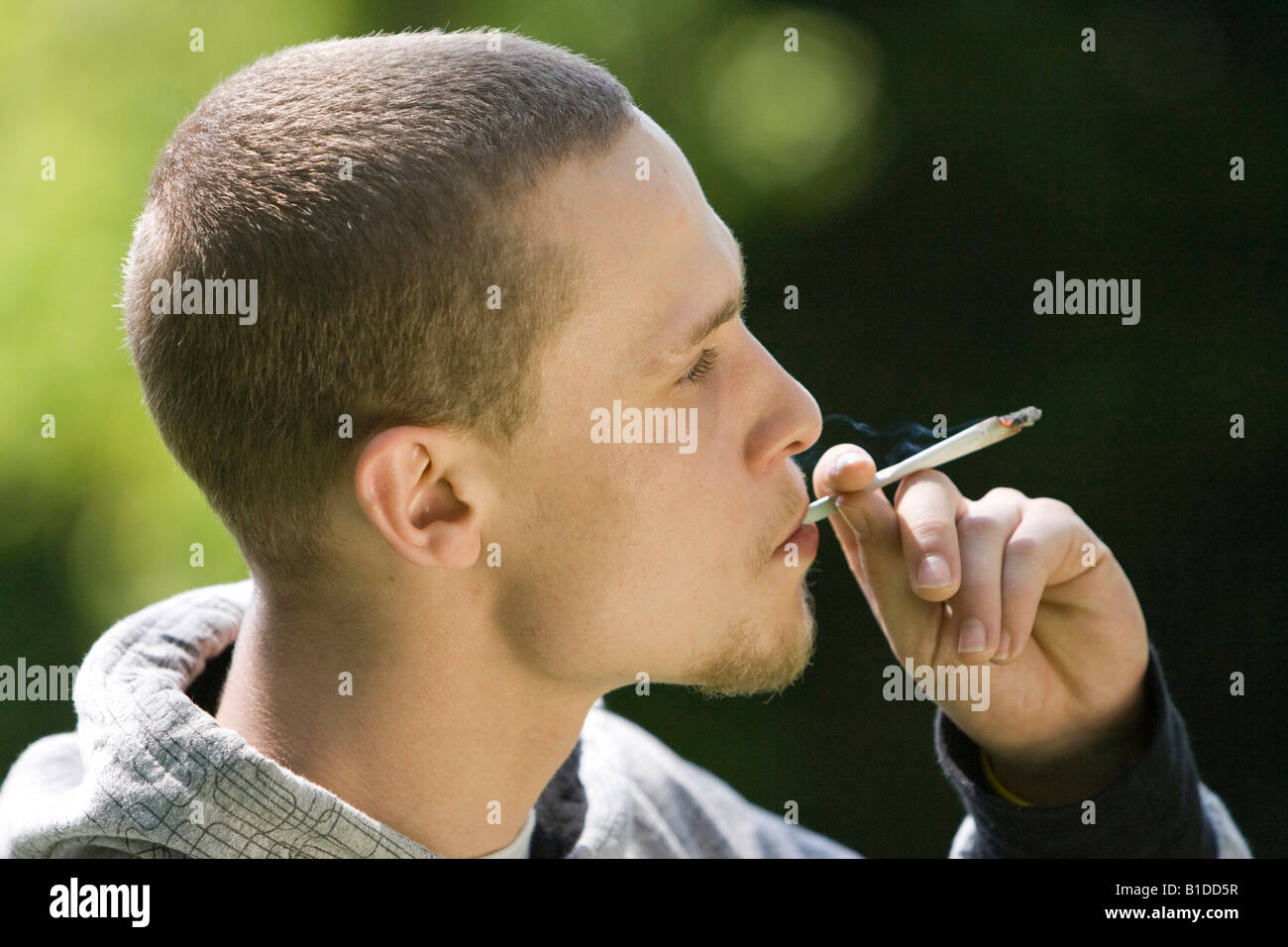 young man smoking cigarette outside - Stock Image