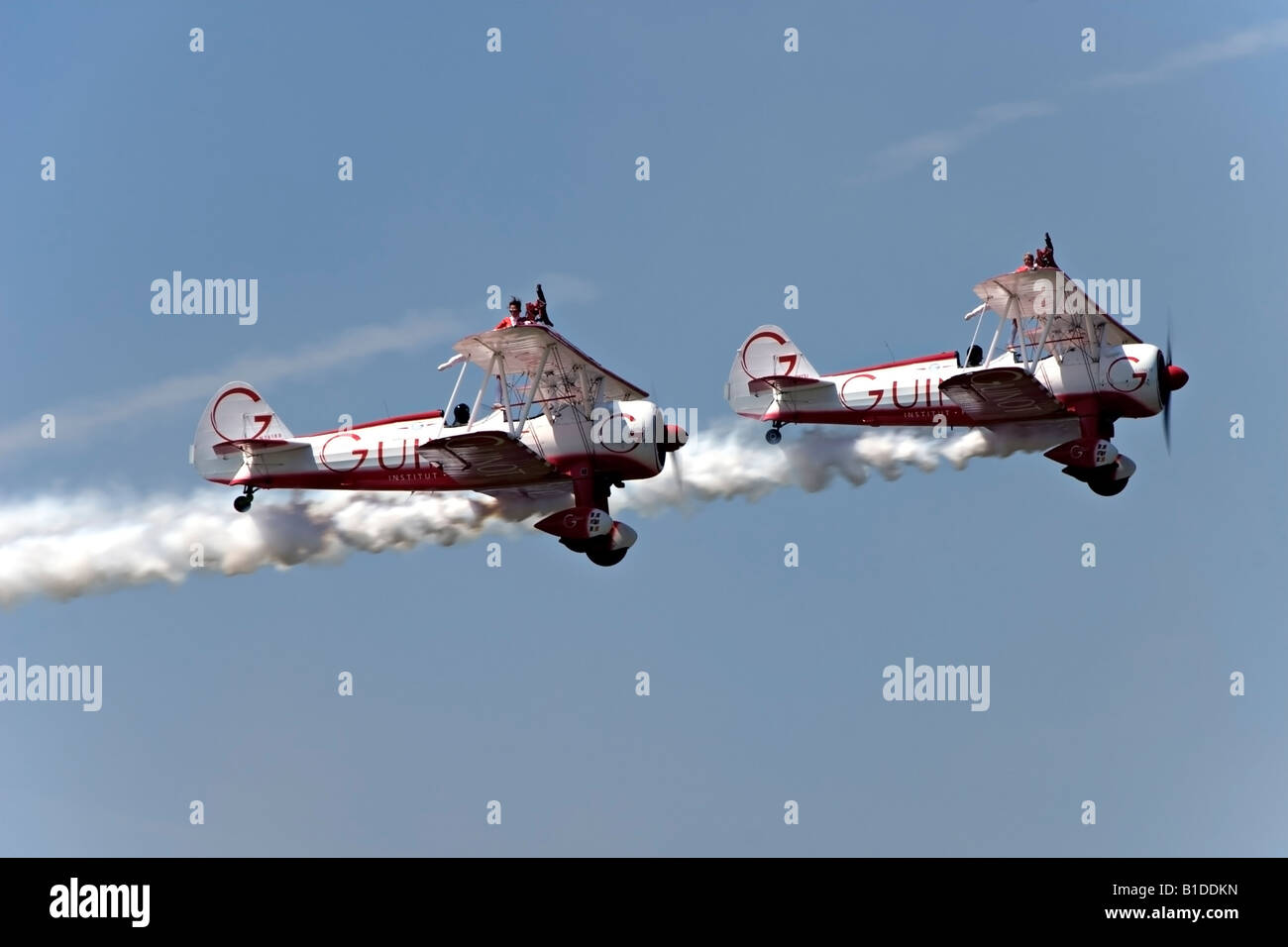 Two Boeing Stearman biplanes from Team Guinot perform their wingwalking feats at the Biggin Hill Airshow - Stock Image