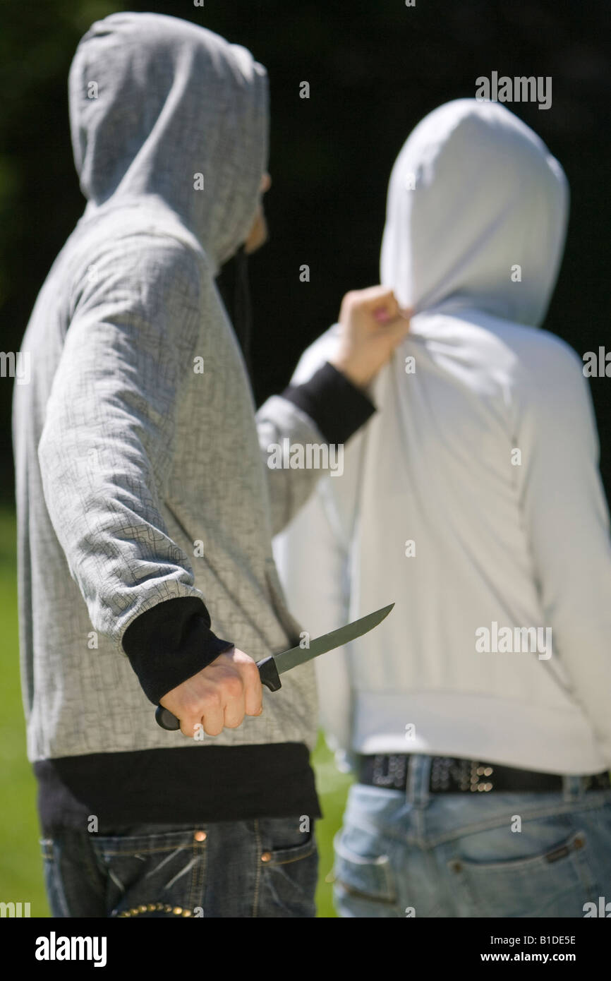 young man holding a knife behind a victim Stock Photo