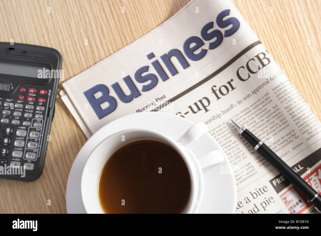 Coffee calculator pen and newspaper on table Stock Photo