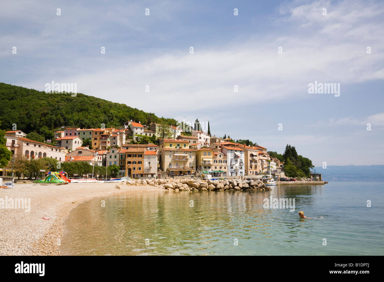 View along quiet beach to harbour and old town buildings on hillside in tourist resort. Moscenicka Draga Istria - Stock Image