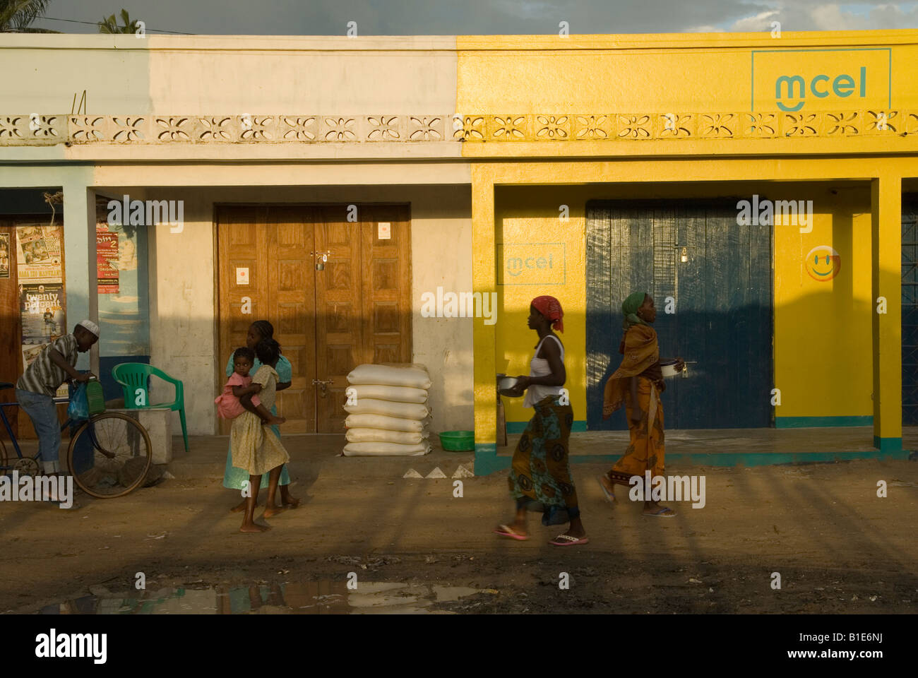 Unpaved street in the late afternoon after a rain shower near the market of Mocimboa da Praia, northern Mozambique - Stock Image