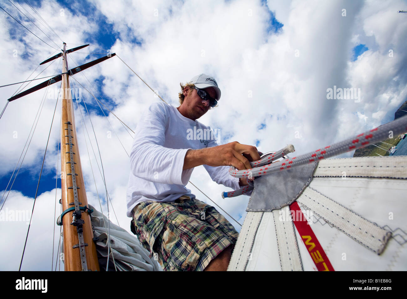 A crew member ties a bowline to secure the head sail during the 2008 Antigua Classic Yacht Regatta - Stock Image