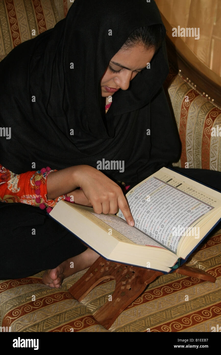 Moslem lady reading the holy Quran at her home in India - Stock Image