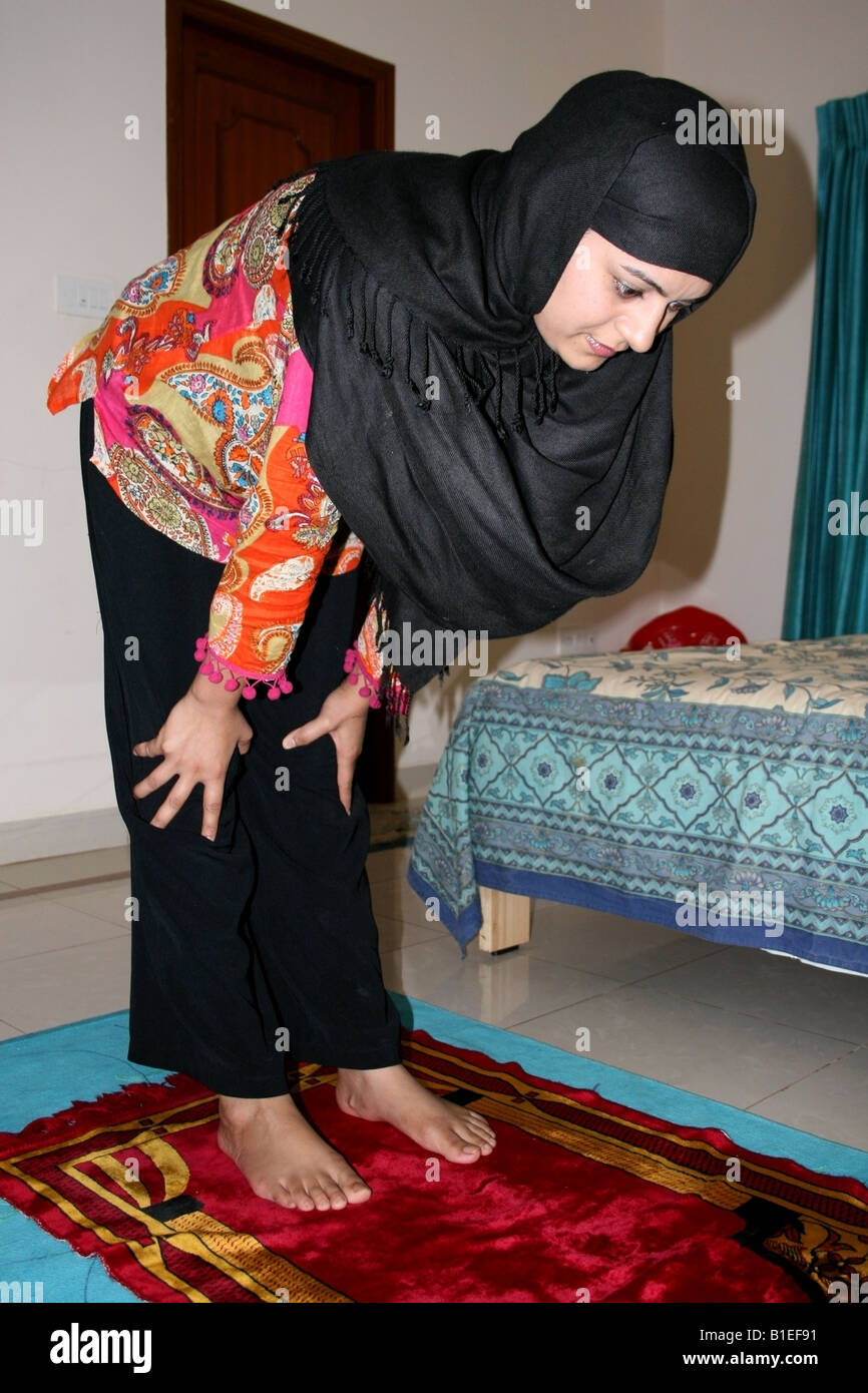 Moslem woman performing the Islamic prayer position number 3 known as Ruku ( bowing down ) - Stock Image