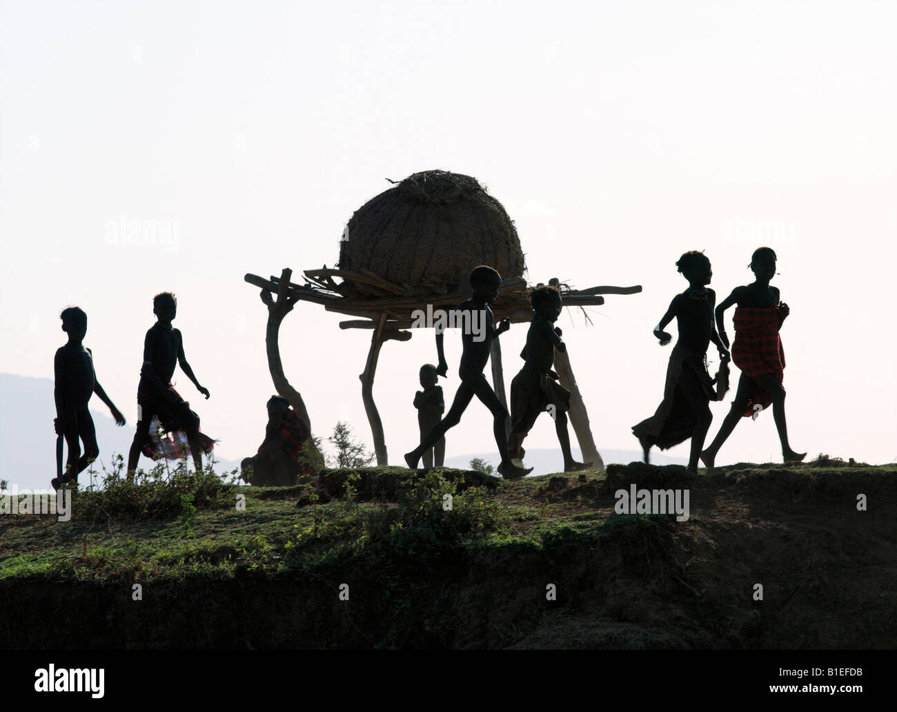 In the late afternoon, a group of Dassanech children hurry home along a bank of the Omo River in Southwest Ethiopia. - Stock Image