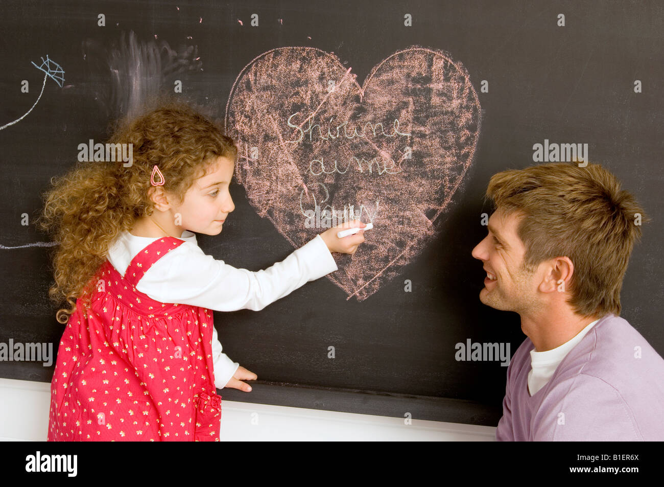 side profile of a girl drawing on the blackboard with her father