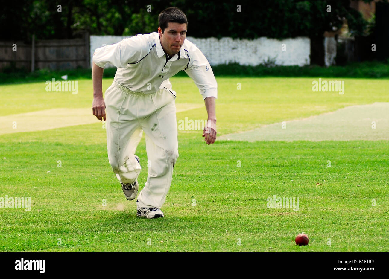 Player fielding during an amateur cricket game, Isleworth, Middlesex, UK. - Stock Image