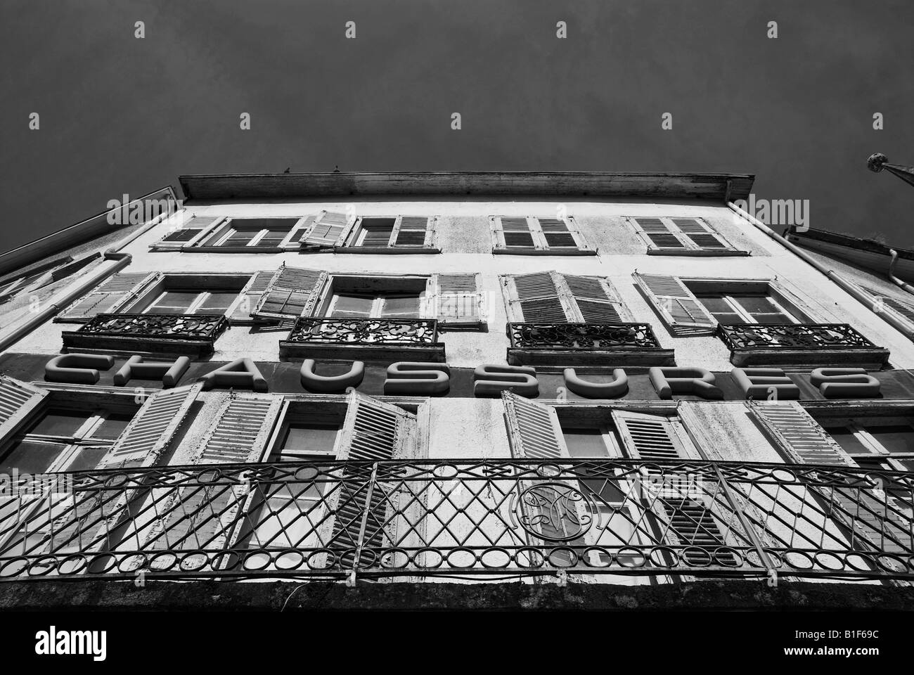 Stock photo of an old shuttered windowed shoe shop The photo was taken in the city of Limoges in France - Stock Image