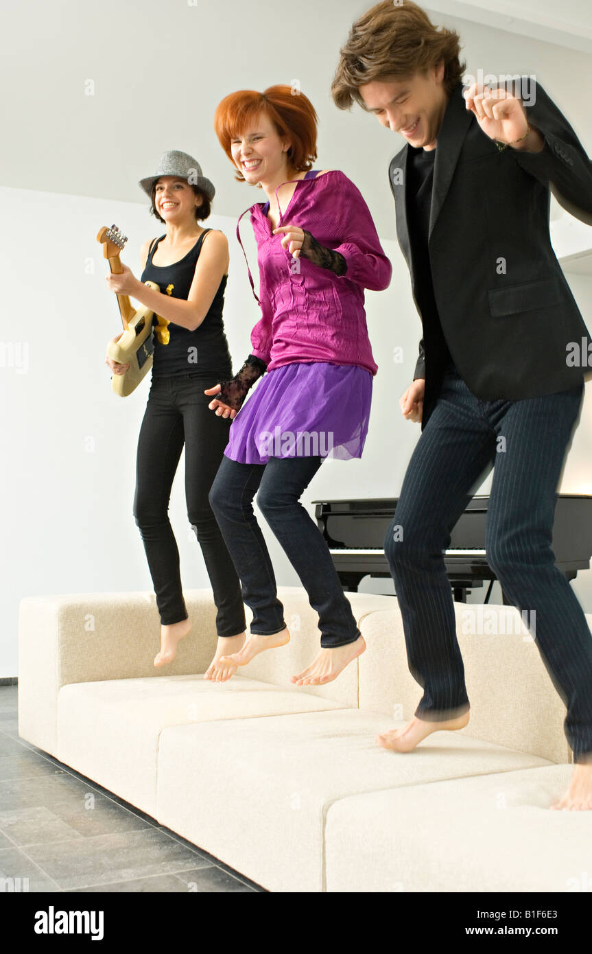 Two young women and a teenage boy dancing on a couch - Stock Image