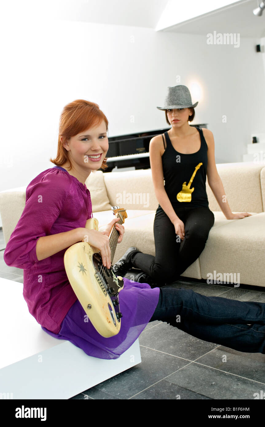 Portrait of a young woman playing a guitar with another young woman sitting beside her - Stock Image