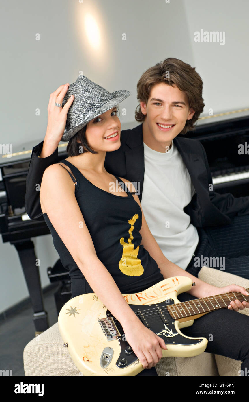 Portrait of a young woman holding a guitar with a teenage boy sitting beside her - Stock Image