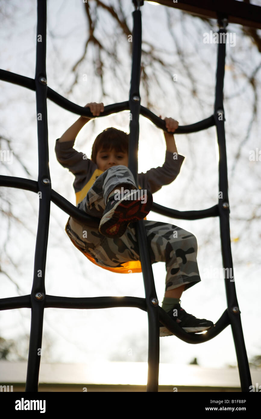 Six year old boy climbs on playground equipment New Zealand - Stock Image