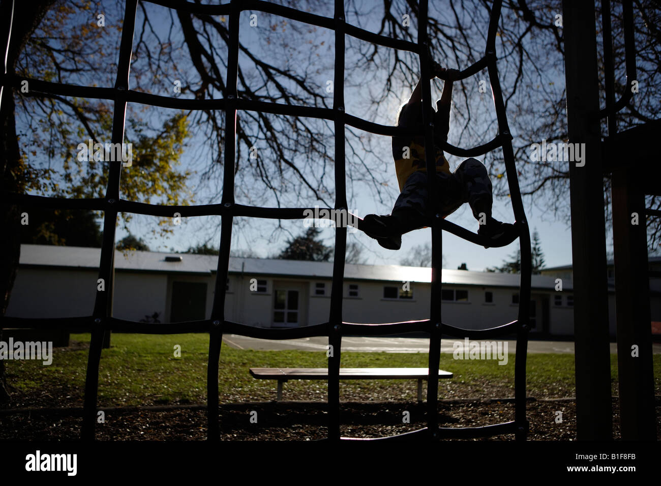 Six year old boy climbs on playground equipment New Zealand Stock Photo