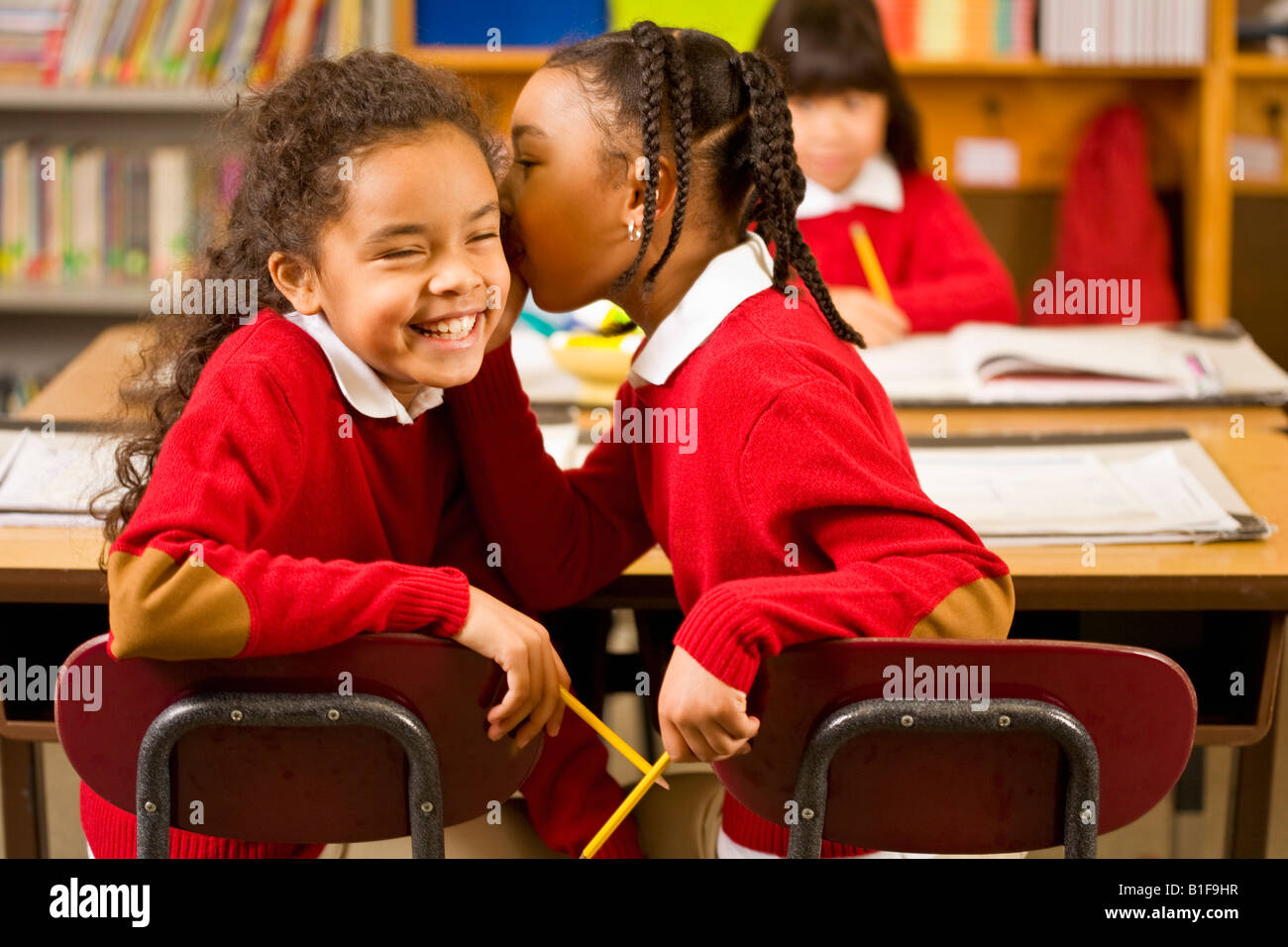 African girls telling secret in classroom - Stock Image