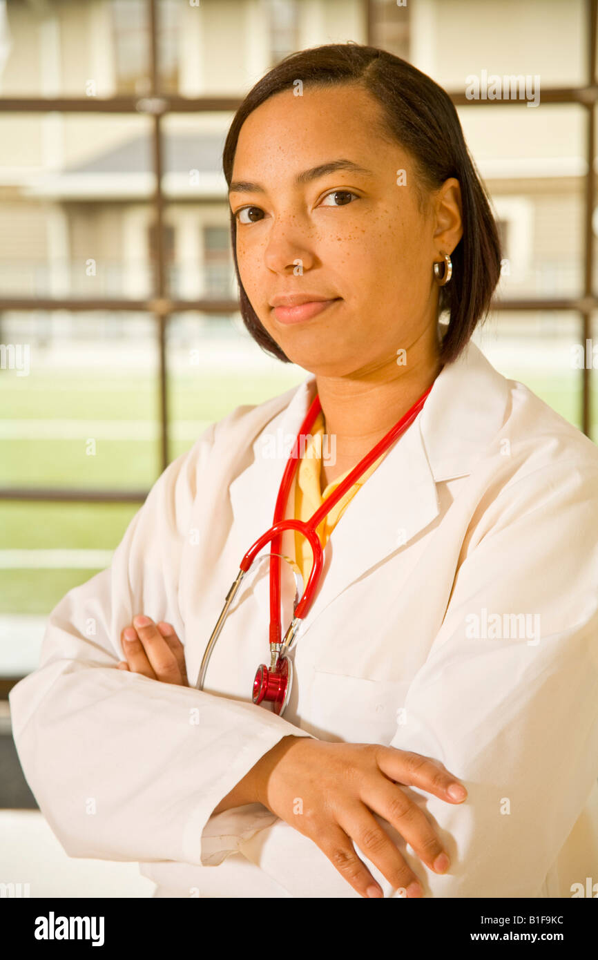 African female doctor with arms crossed - Stock Image